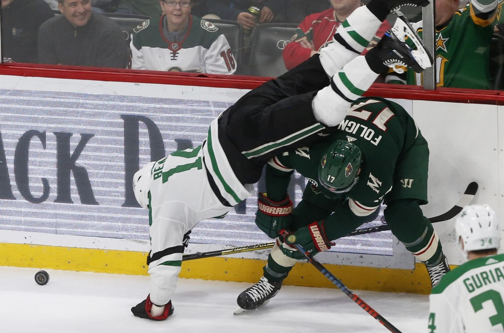 Dallas Stars' Jamie Benn, left, topples over Minnesota Wild's Marcus Foligno during a race for the puck in the first period of an NHL hockey game Satu...