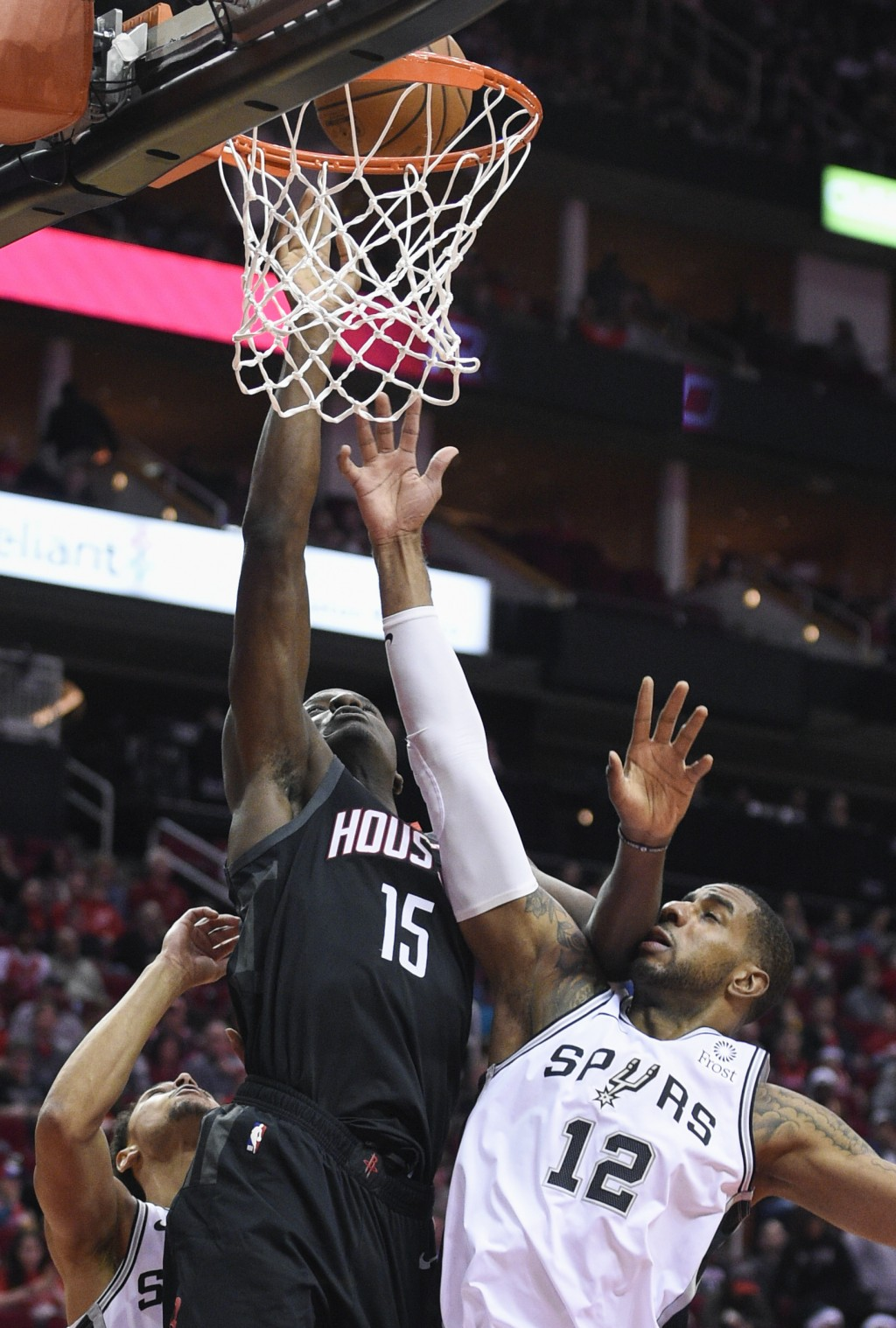 Houston Rockets center Clint Capela (15) and San Antonio Spurs forward LaMarcus Aldridge (12) vie for a rebound during the first half of an NBA basket...