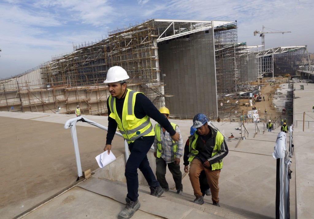 In this Sunday, Dec. 16, 2018 photo, workers go for a break at the Grand Egyptian Museum under construction in Giza, Egypt. Thousands of Egyptians are...