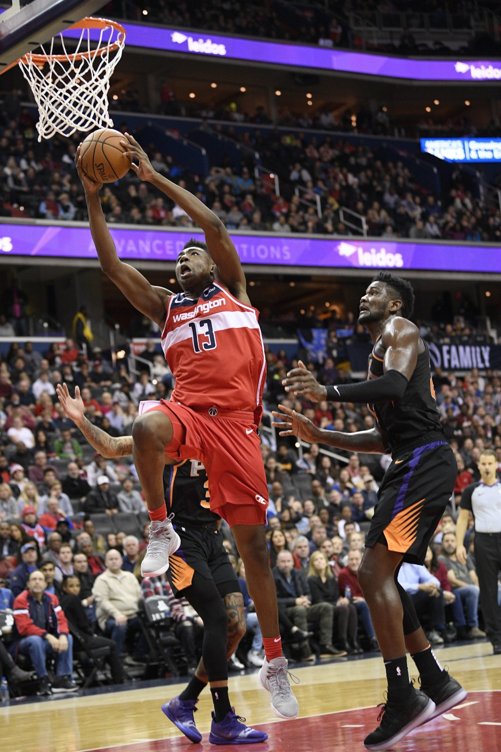 Washington Wizards center Thomas Bryant (13) goes to the basket past Phoenix Suns center Deandre Ayton, right, during overtime of an NBA basketball ga...