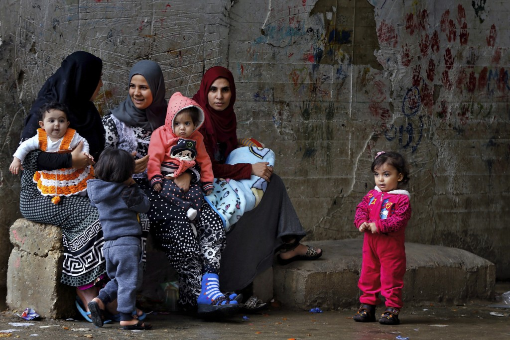 In this Tuesday, Dec. 18, 2018, photo, Syrian refugees women hold their children as they sit in Ouzai refugee compound, in the southern port city of S...