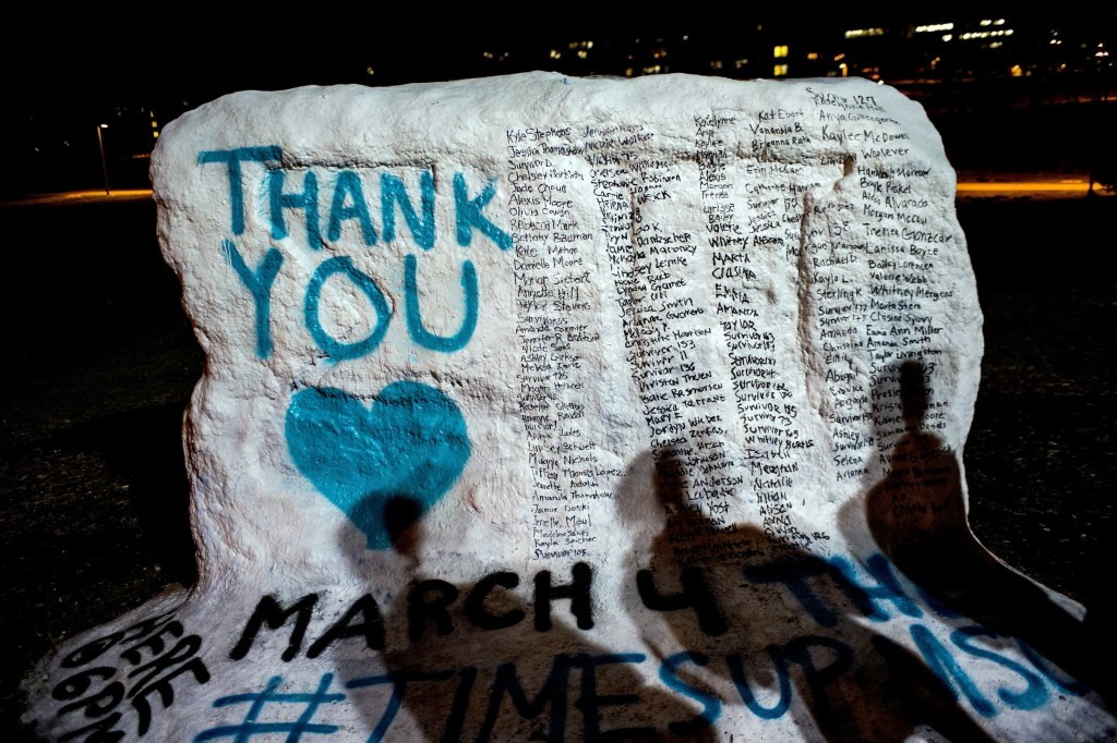 """FILE - In this Jan. 26, 2018, file photo, the shadows of Michigan State University students appear on """"the rock"""" in the university campus which was pa..."""