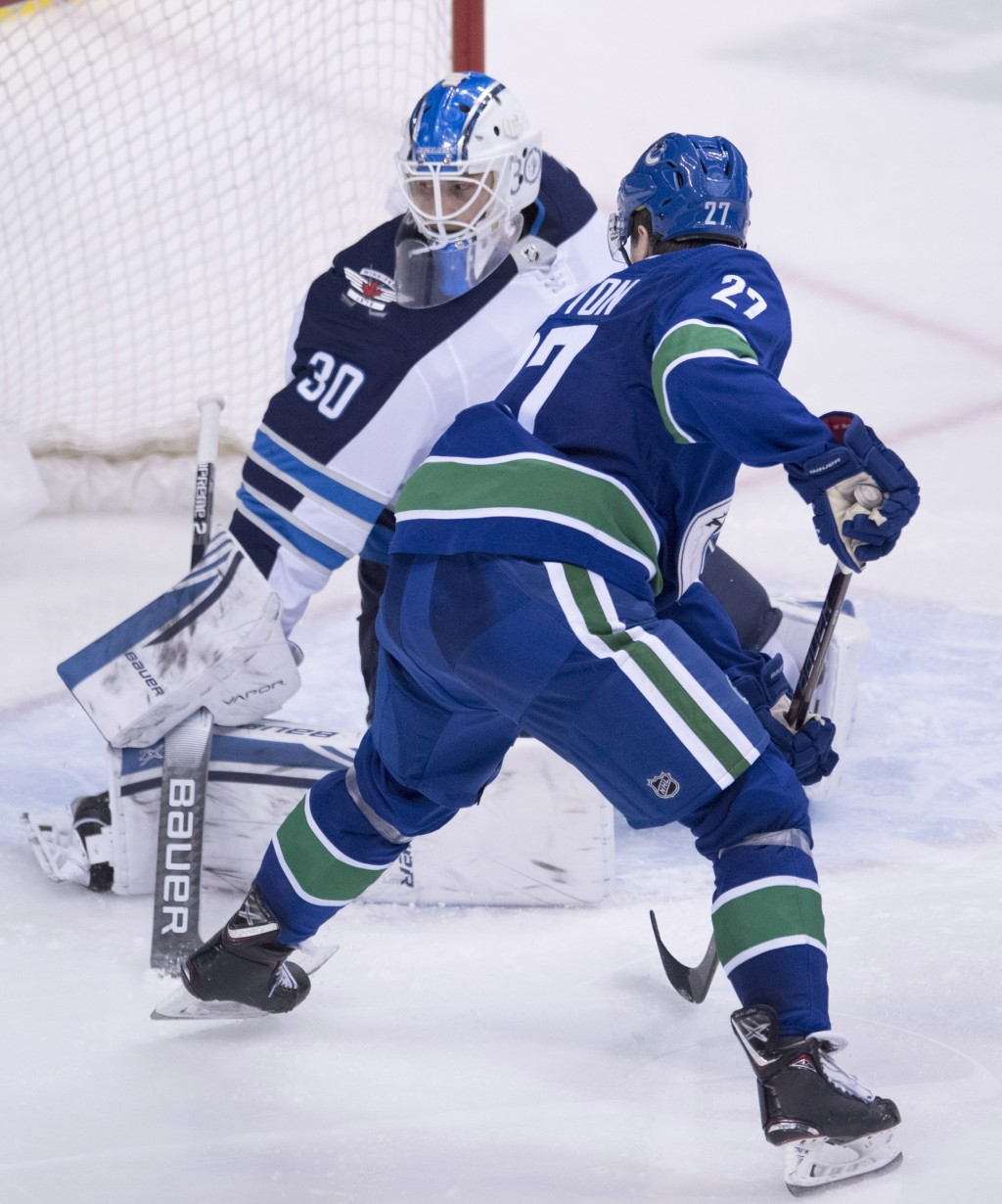 Vancouver Canucks defenseman Ben Hutton (27) tries to get a shot past Winnipeg Jets goaltender Laurent Brossoit (30) during the third period of an NHL...