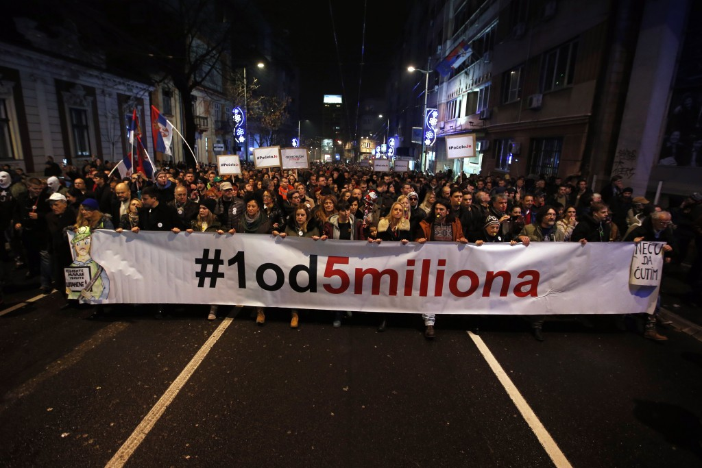 People hold a banner that reads: ''#1 out of 5 million'' during a protest against populist President Aleksandar Vucic in Belgrade, Serbia, Saturday, D...