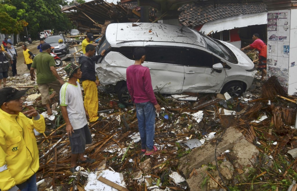 In this Sunday, Dec. 23, 2018, photo, people inspect the wreckage of a car swept away by a tsunami in Carita, Indonesia. The tsunami that hit the coas...
