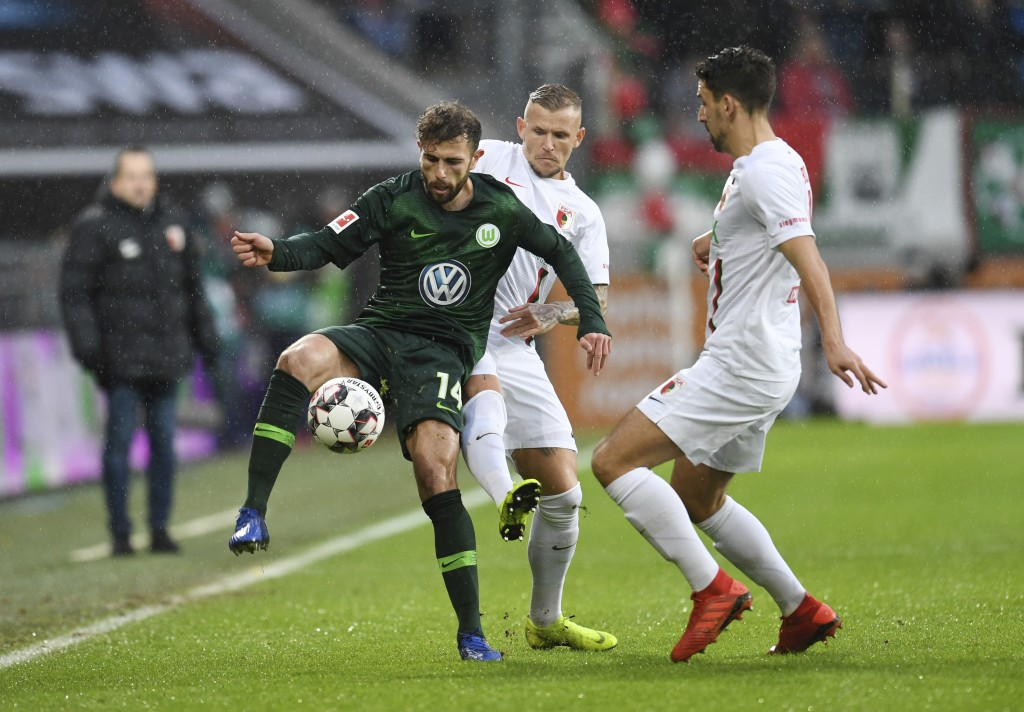 Wolfsburg's Admir Mehmedi, left, and Augsburg's Jonathan Schmid, center, challenge for the ball during the German Bundeliga soccer match between FC Au