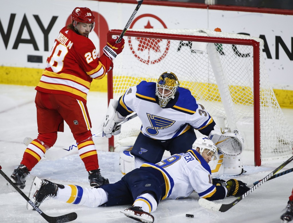 St. Louis Blues' Jay Bouwmeester, right, dives in front of the puck as goalie Jake Allen, center, and Calgary Flames' Elias Lindholm, of Sweden, watch