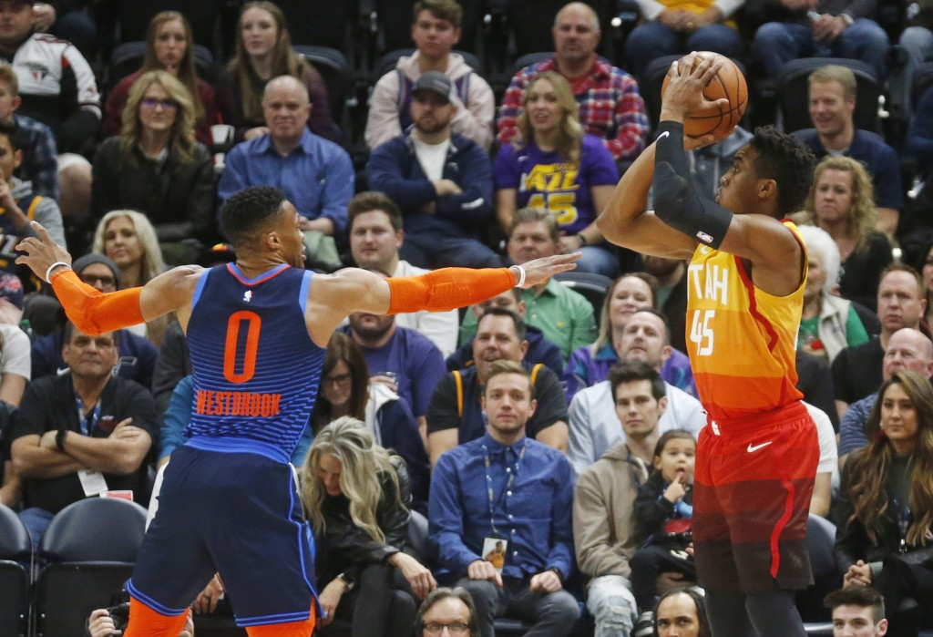 Utah Jazz guard Donovan Mitchell (45) shoots as Oklahoma City Thunder guard Russell Westbrook (0) defends in the first half of an NBA basketball game,...