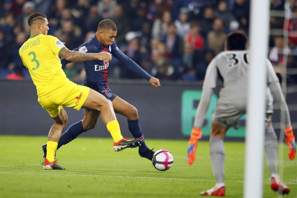 PSG forward Kylian Mbappe, center, vies with Nantes' Diego Carlos, left, during the League One soccer match between Paris Saint Germain and Nantes at