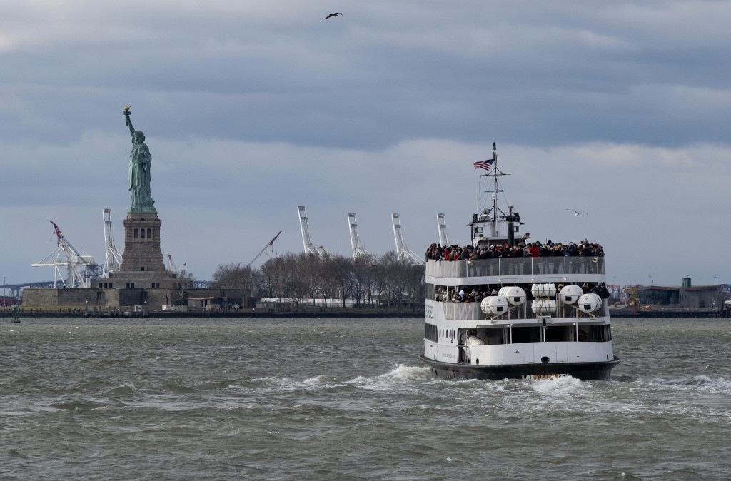 A ferry full of passengers steams towards the Statue of Liberty Saturday, Dec. 22, 2018, in New York. The national landmark remained open despite a pa...