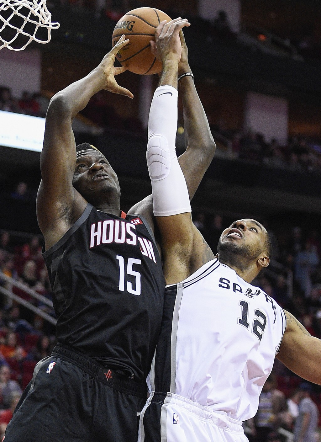 Houston Rockets center Clint Capela (15) and San Antonio Spurs forward LaMarcus Aldridge vie for a rebound during the first half of an NBA basketball ...