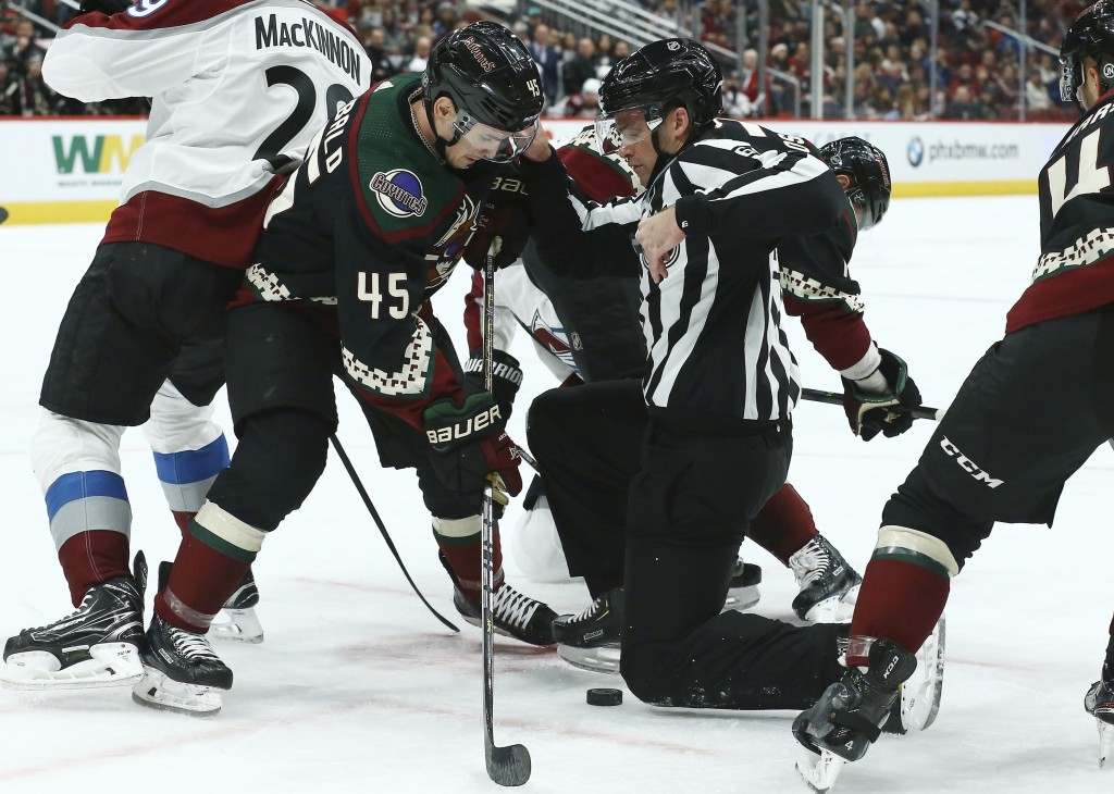 Arizona Coyotes right wing Josh Archibald (45) tries to get to the puck as linesman Brandon Gawryletz moves out of the way during the first period of ...