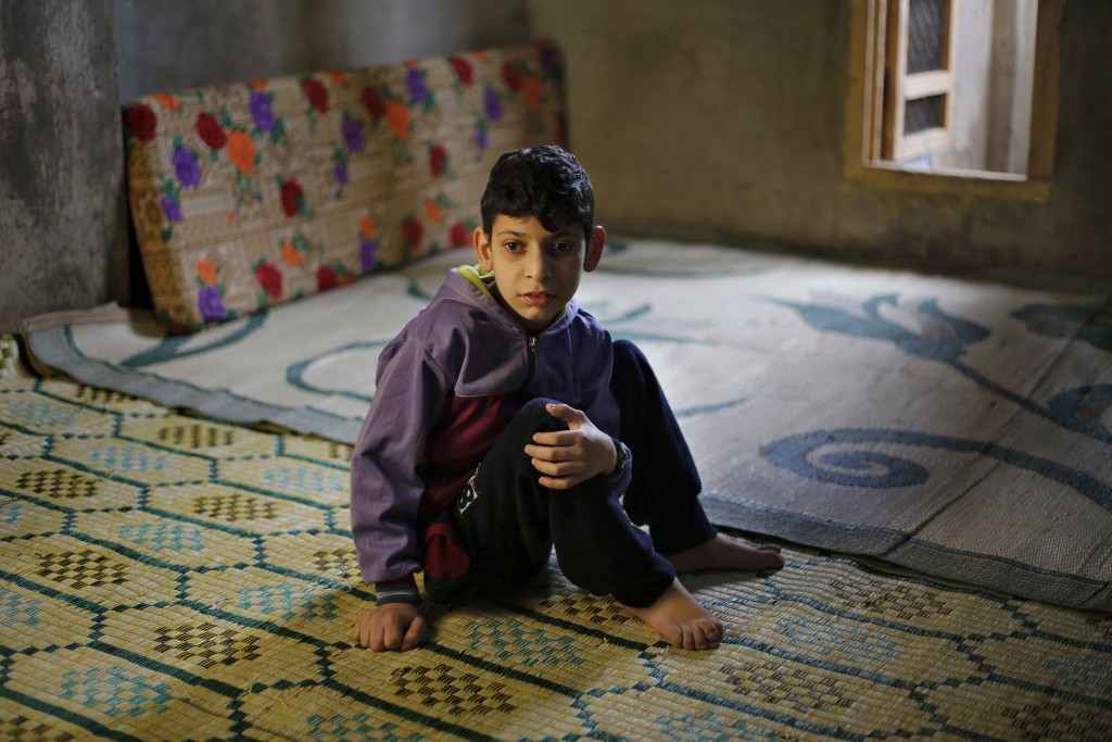 In this Tuesday, Dec. 18, 2018, photo, Syrian refugee Abdul-Rahman Kassar, 12, who has problems walking, sits inside his family home in Ouzai refugee ...