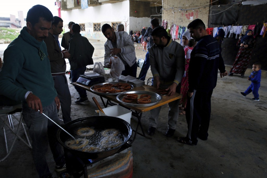 In this Tuesday, Dec. 18, 2018, photo, a Syrian refugee man, left, prepares Syrian sweets to be sold in Ouzai refugee compound, in the southern port c...