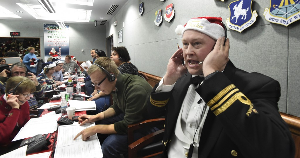 FILE – In this Dec. 24, 2017, file photo, Canadian Lt. Maj. Chris Hache takes a call while volunteering at the NORAD Tracks Santa center at Peterson A...