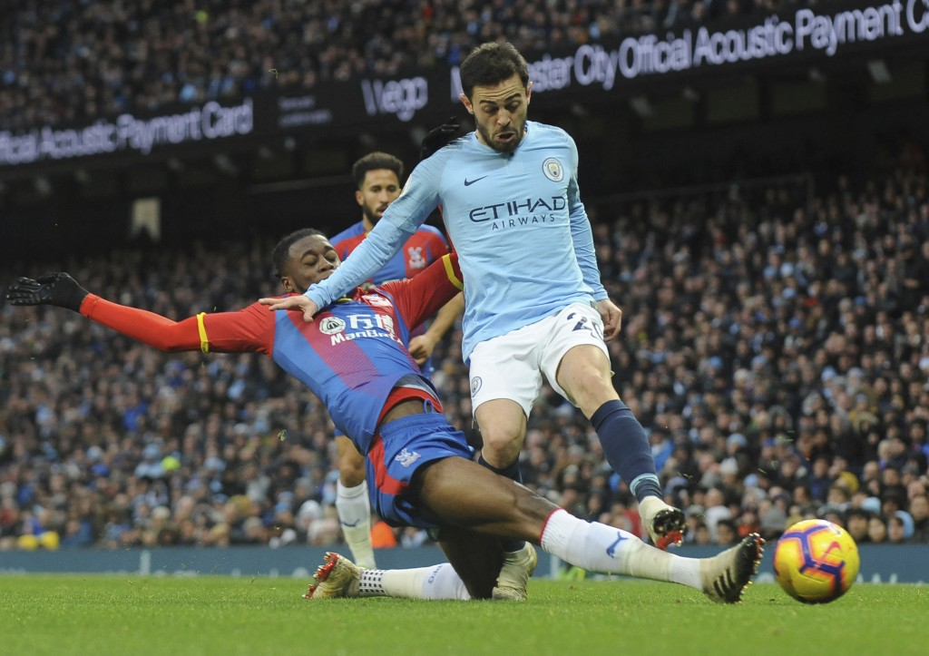 Crystal Palace's Aaron Wan-Bissaka, left, and Manchester City's Bernardo Silva challenge for the ball during the English Premier League soccer match b...