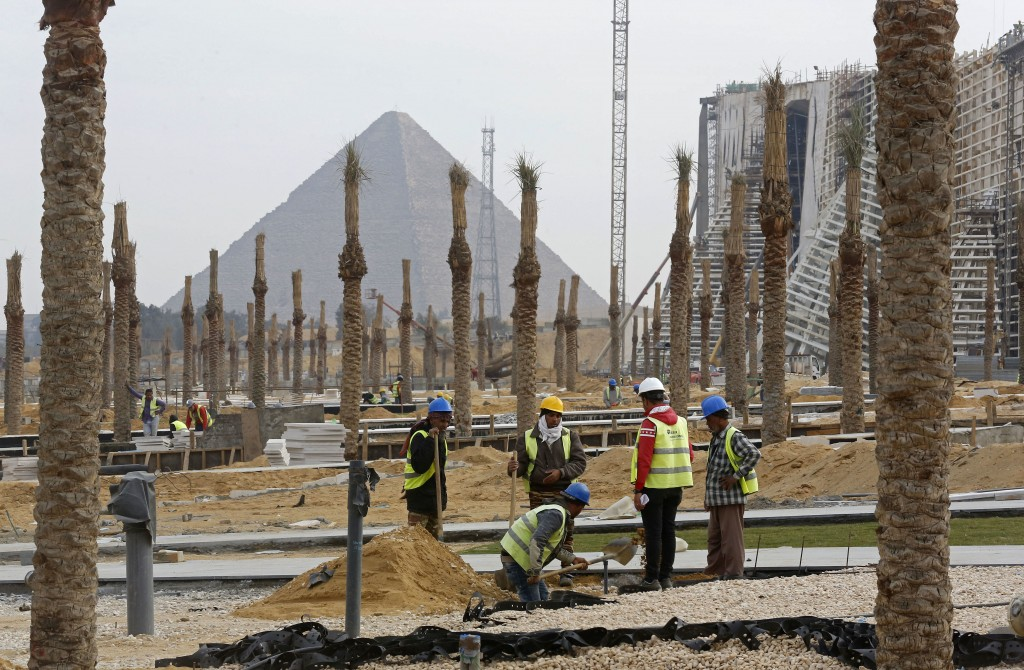 In this Sunday, Dec. 16, 2018 photo, workers landscape grounds at the Grand Egyptian Museum under construction in front of the Pyramids in Giza, Egypt...