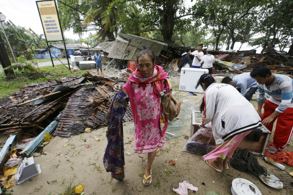 A women inspects her house which was damaged by a tsunami, in Carita, Indonesia, Sunday, Dec. 23, 2018. The tsunami occurred after the eruption of a v...