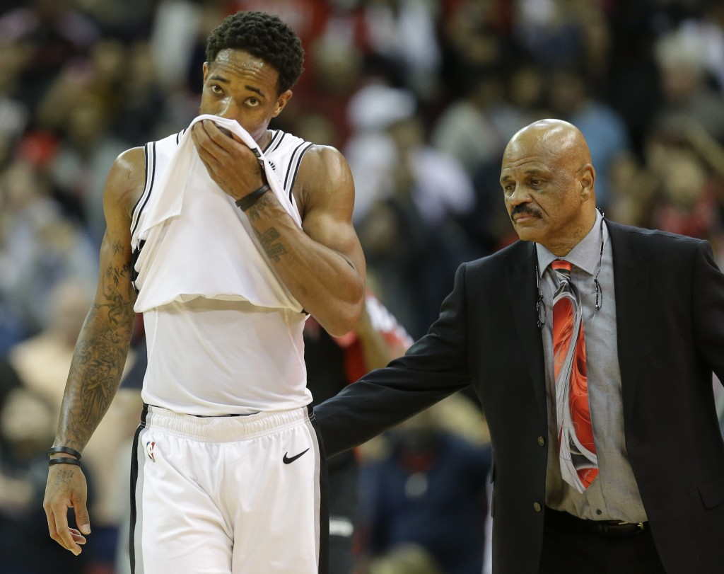 San Antonio Spurs guard DeMar DeRozan, left, walks off the court after the team's loss to the Houston Rockets as Houston player development coach John...