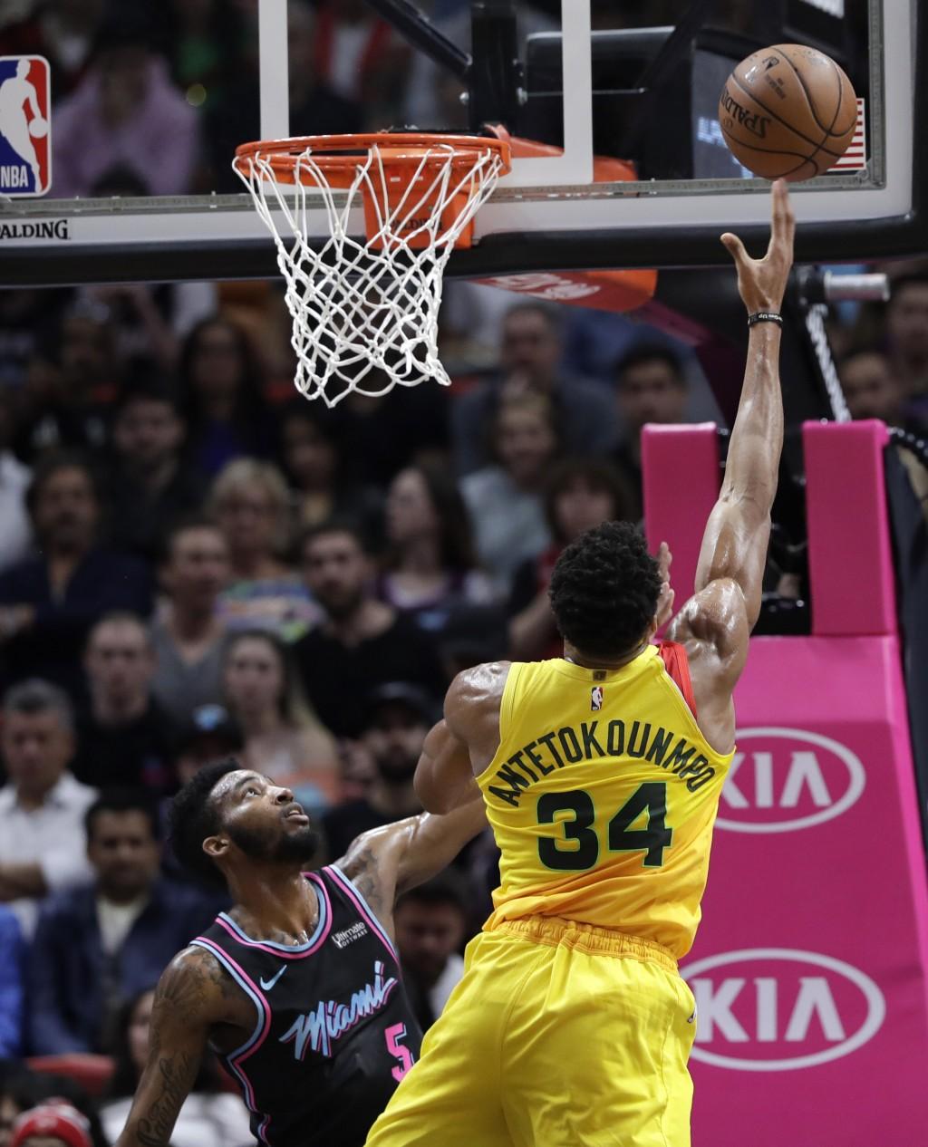 Milwaukee Bucks forward Giannis Antetokounmpo (34) shoots and is fouled by Miami Heat forward Derrick Jones Jr. (5) during the first half of an NBA ba...