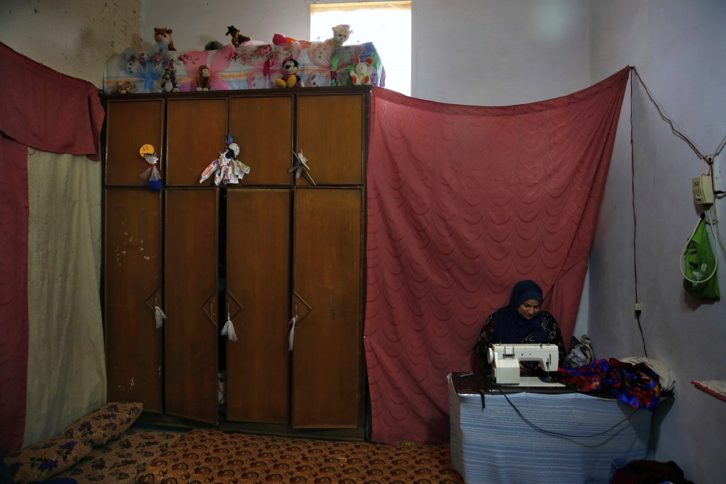 In this Tuesday, Dec. 18, 2018, photo, Syrian refugee Dawlat Saleh sews clothes at her home in Ouzai refugee compound, in the southern port city of Si...