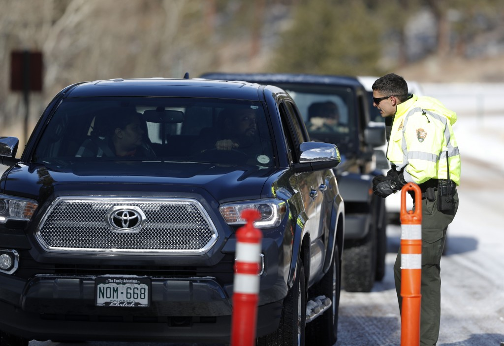 Park ranger Dillon O'Brien stops motorists as they try to navigate the snow packed road to Bear Lake in Rocky Mountain National Park Saturday, Dec. 22