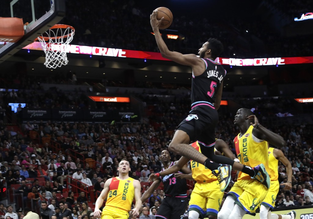 Miami Heat forward Derrick Jones Jr. (5) goes up to shoot over Milwaukee Bucks guard Pat Connaughton (24) and forward Thon Maker, right, during the fi...