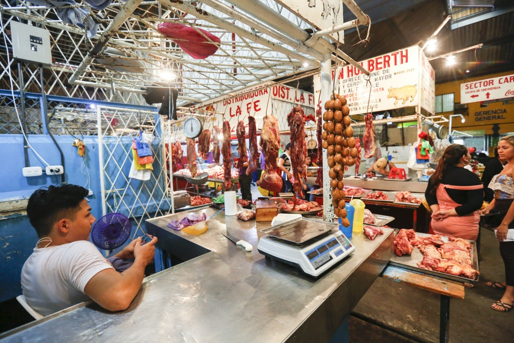 In this Dec. 21, 2018 photo, a vendor waits for customers at a market in Managua, Nicaragua. In the streets of Managua, outward appearances suggest so