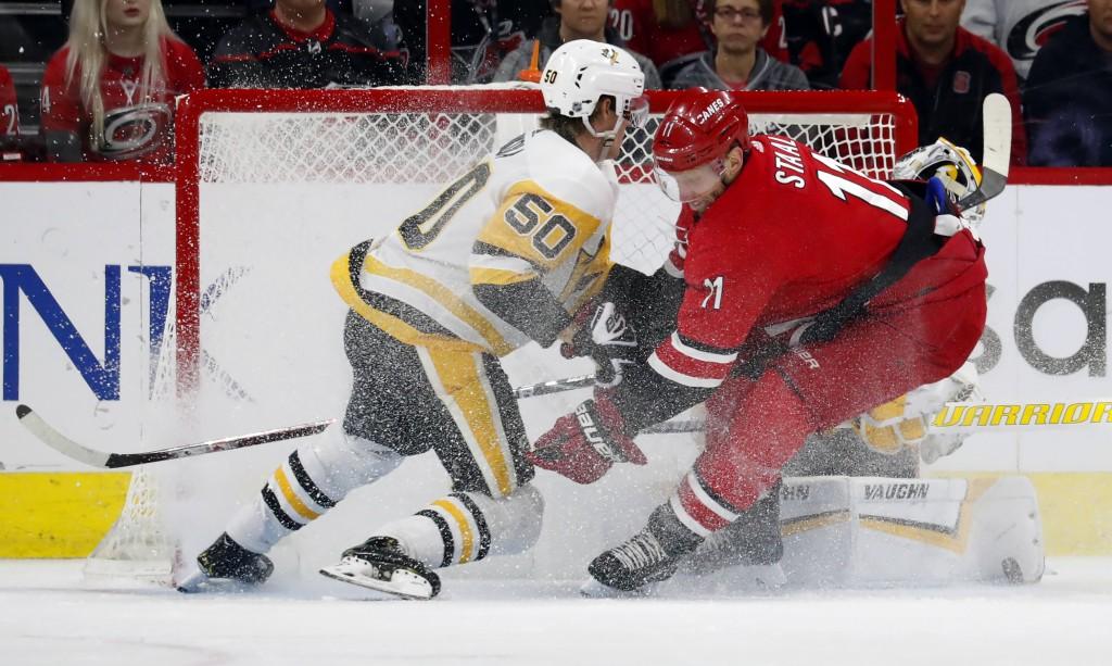 Carolina Hurricanes' Jordan Staal (11) crashes into Pittsburgh Penguins' Juuso Riikola (50) and goaltender Matt Murray (30) during the first period of...