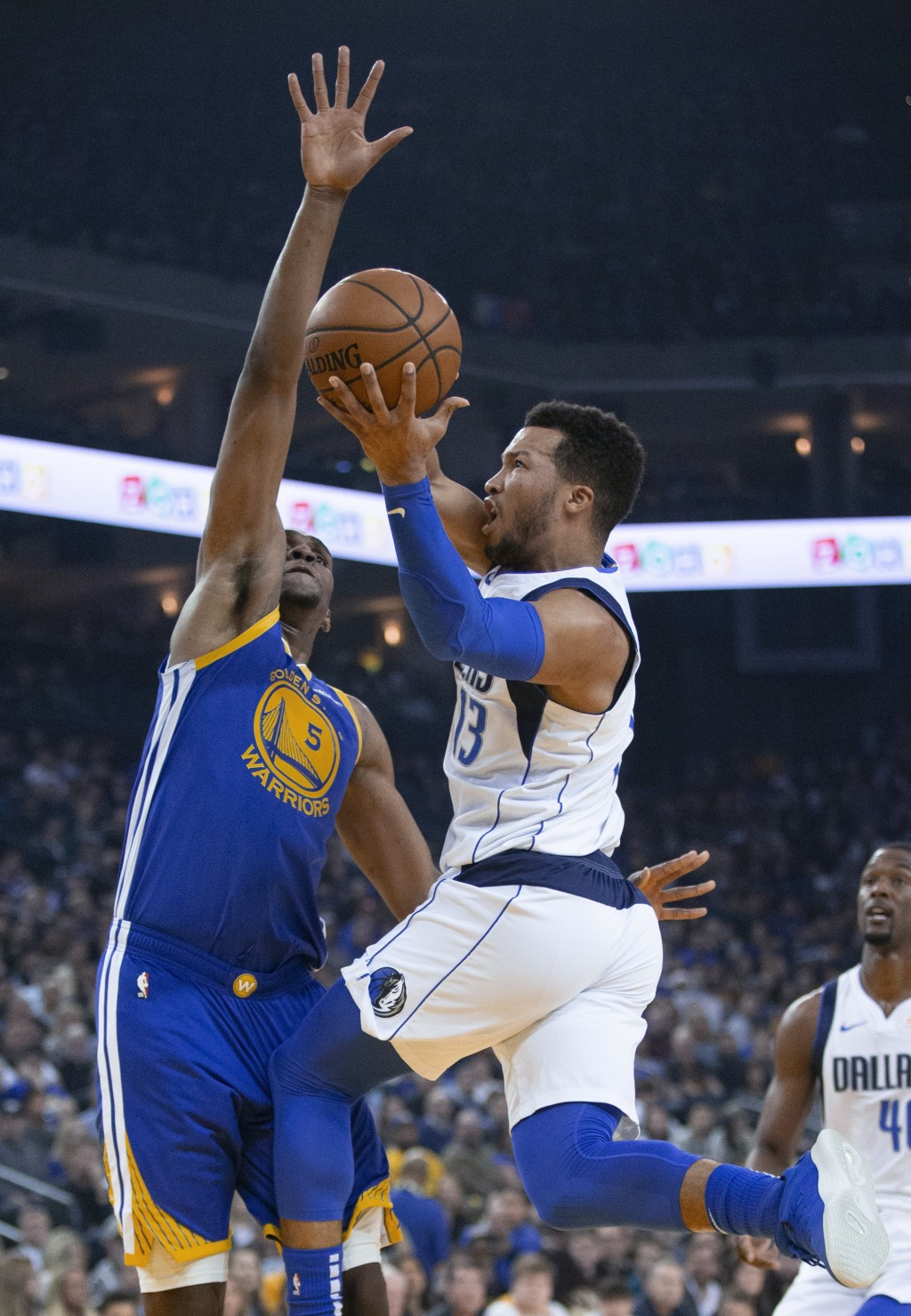 Dallas Mavericks' Jalen Brunson (13) is fouled by Golden State Warriors' Kevon Looney (5) as he drives to the basket during the first quarter of an NB...
