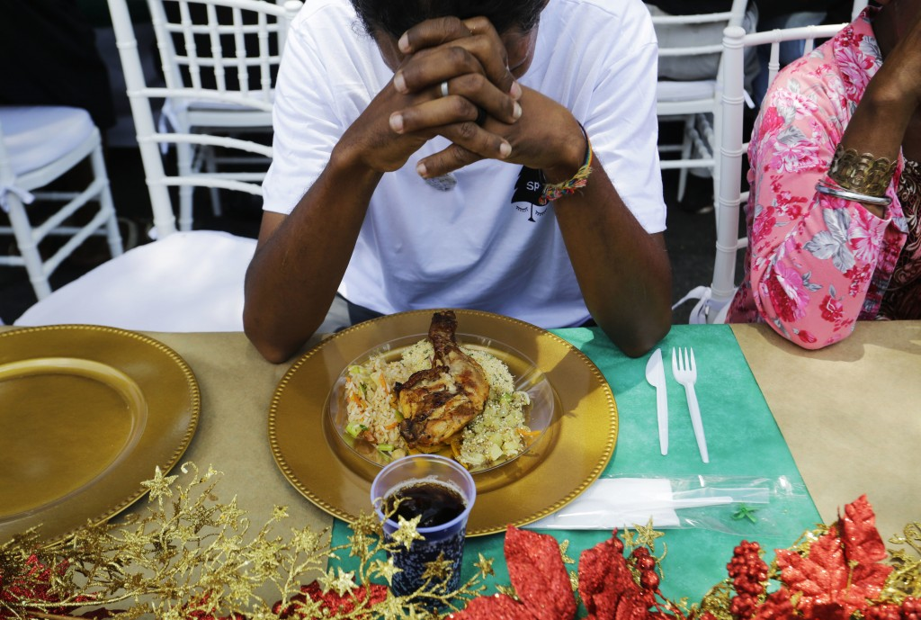 A homeless person prays before eating during a Christmas lunch served to homeless people by the non-governmental organization SP Invisivel in downtown