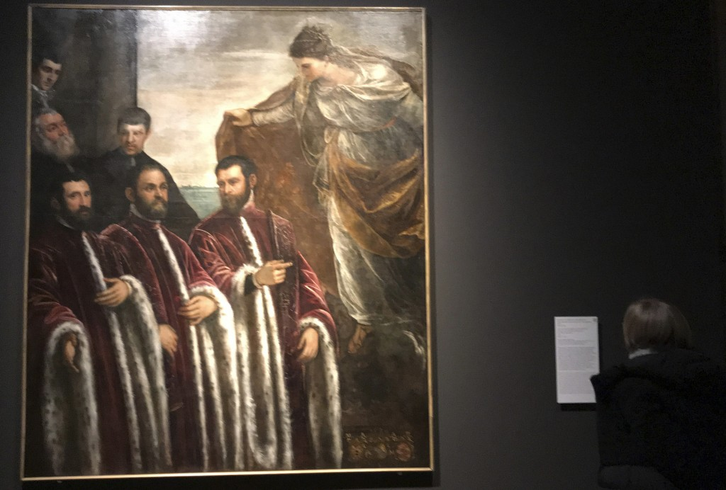 """In this Dec. 3, 2018 photo, a visitor to an exhibition of Tintoretto works looks at his """"St. Justina with Three Treasurers and Their Secretaries"""" at t..."""