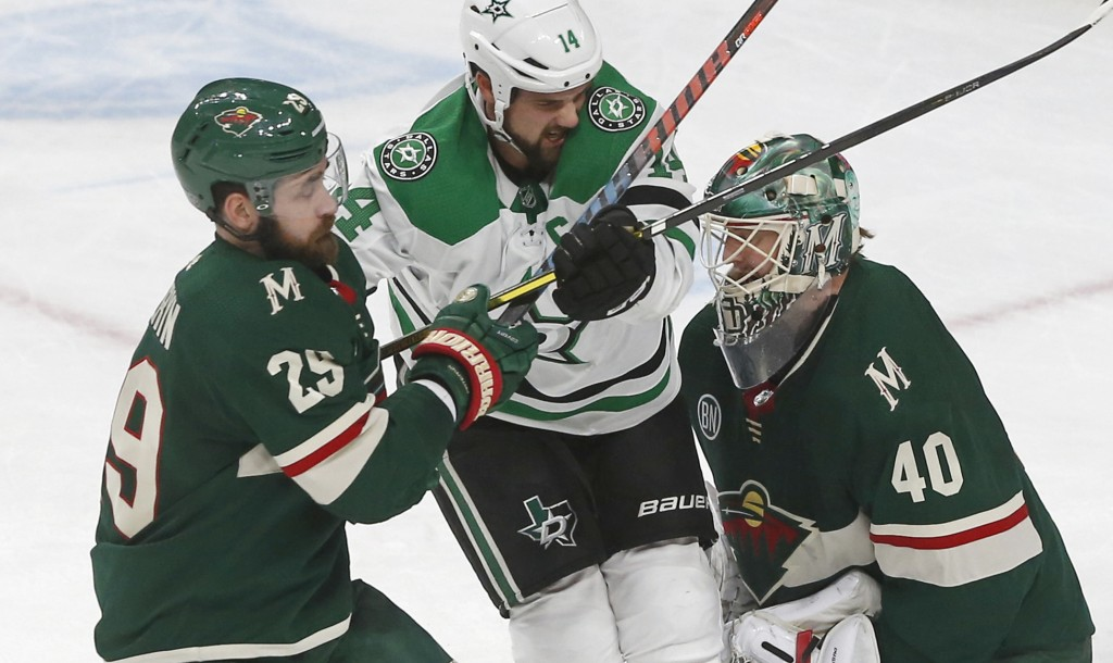 Dallas Stars' Jamie Benn, center, gets squeezed between Minnesota Wild's Greg Pateryn, left, and goalie Devan Dubnyk in the first period of an NHL hoc...