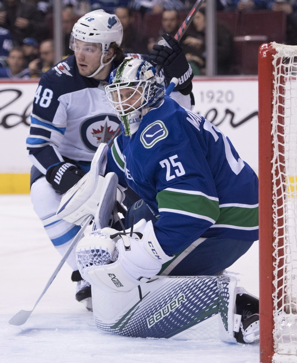 Winnipeg Jets left wing Brendan Lemieux (48) tries to get a shot past Vancouver Canucks goaltender Jacob Markstrom (25) during first-period NHL hockey...
