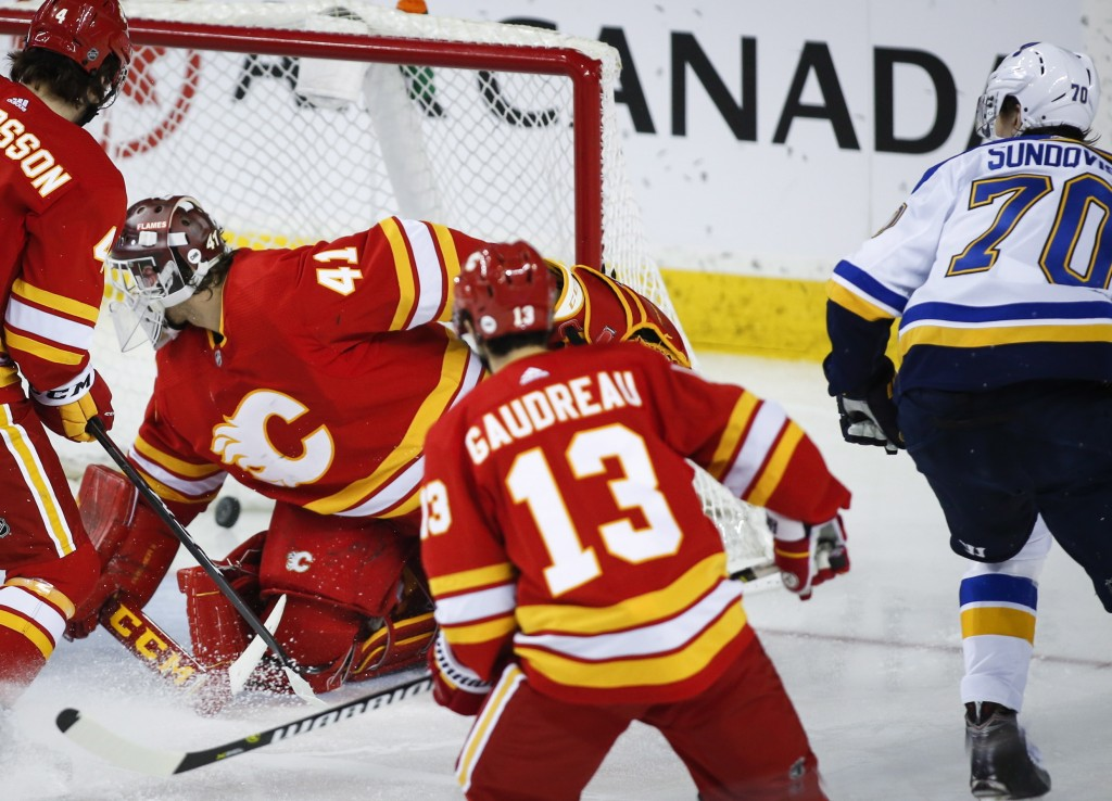 St. Louis Blues' Oskar Sundqvist, right, of Sweden, scores against Calgary Flames goalie Mike Smith during third-period NHL hockey game action in Calg