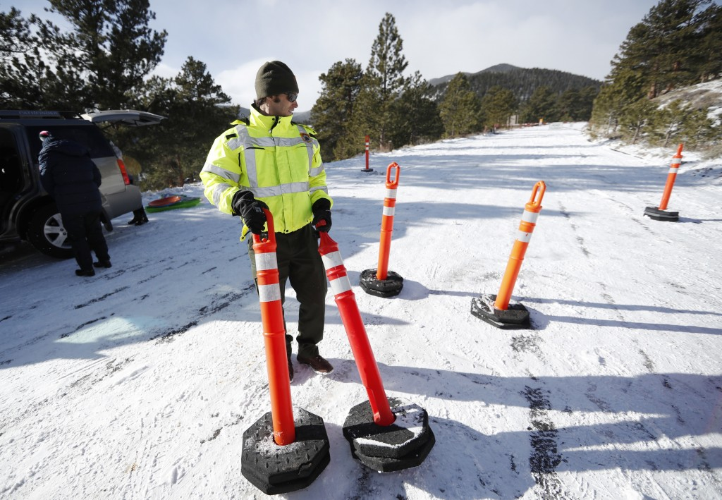 Park ranger Kevin Sturmer drags pylons up Trail Ridge Road to block access after an overnight snow was left unplowed in Rocky Mountain National Park S...