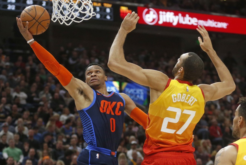Oklahoma City Thunder guard Russell Westbrook (0) lays the ball up as Utah Jazz center Rudy Gobert (27) defends in the first half of an NBA basketball...