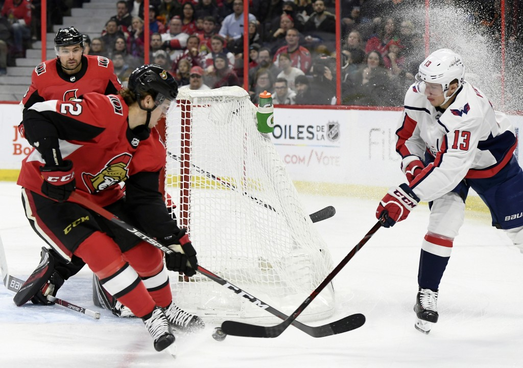 Washington Capitals left wing Jakub Vrana (13) plays the puck behind the net as Ottawa Senators defenseman Thomas Chabot (72) defends during the first...