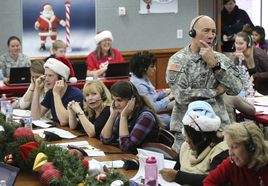 FILE - In this Dec. 24, 2014, file photo, NORAD Chief of Staff Maj. Gen. Charles D. Luckey takes a call while volunteering at the NORAD Tracks Santa c...