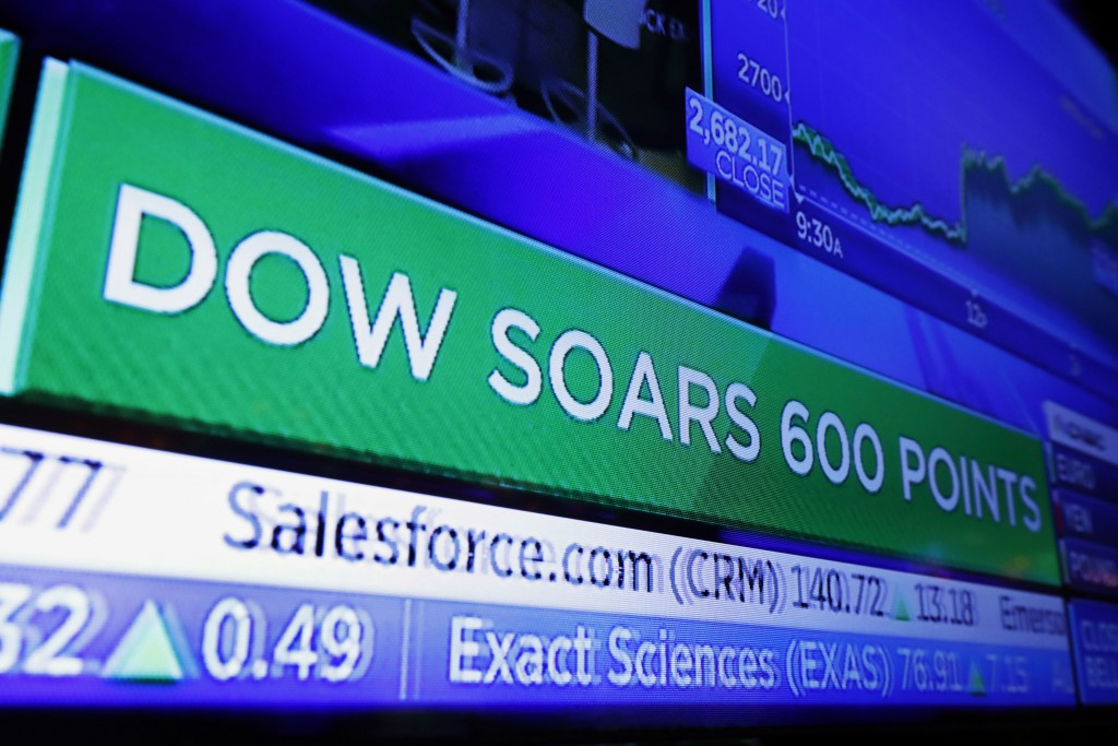 FILE - In this Nov. 28, 2018, file photo, a television screen on the floor of the New York Stock Exchange shows a headline for the Dow Jones industria