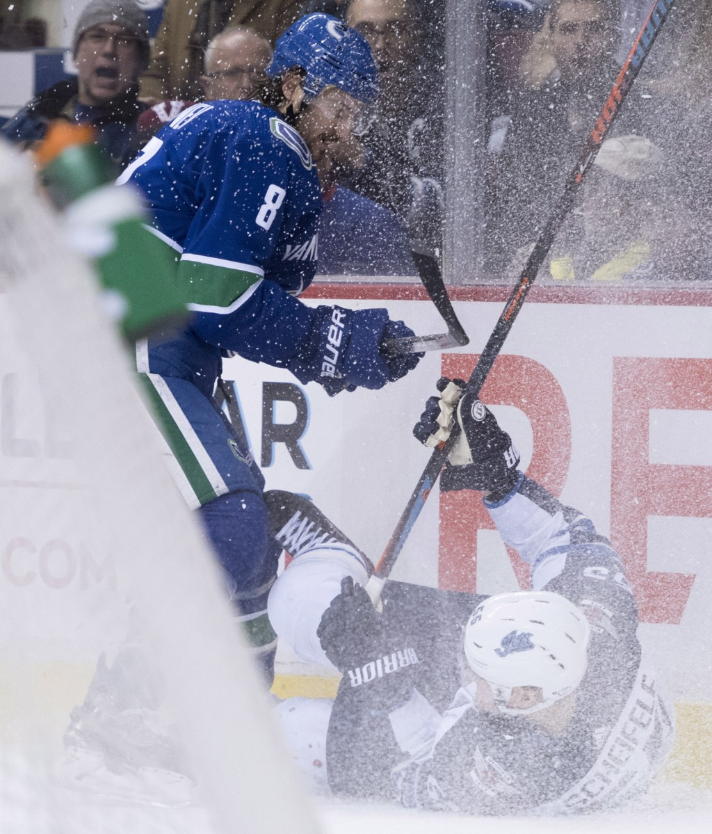 Vancouver Canucks defenseman Christopher Tanev (8) fights for control of the puck with Winnipeg Jets center Mark Scheifele (55) during first-period NH...