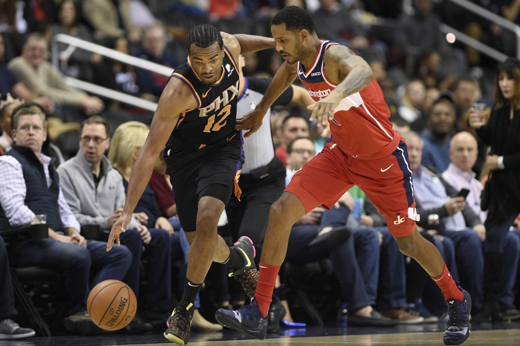 Phoenix Suns forward T.J. Warren (12) dribbles the ball against Washington Wizards forward Trevor Ariza (1) during the first half of an NBA basketball...