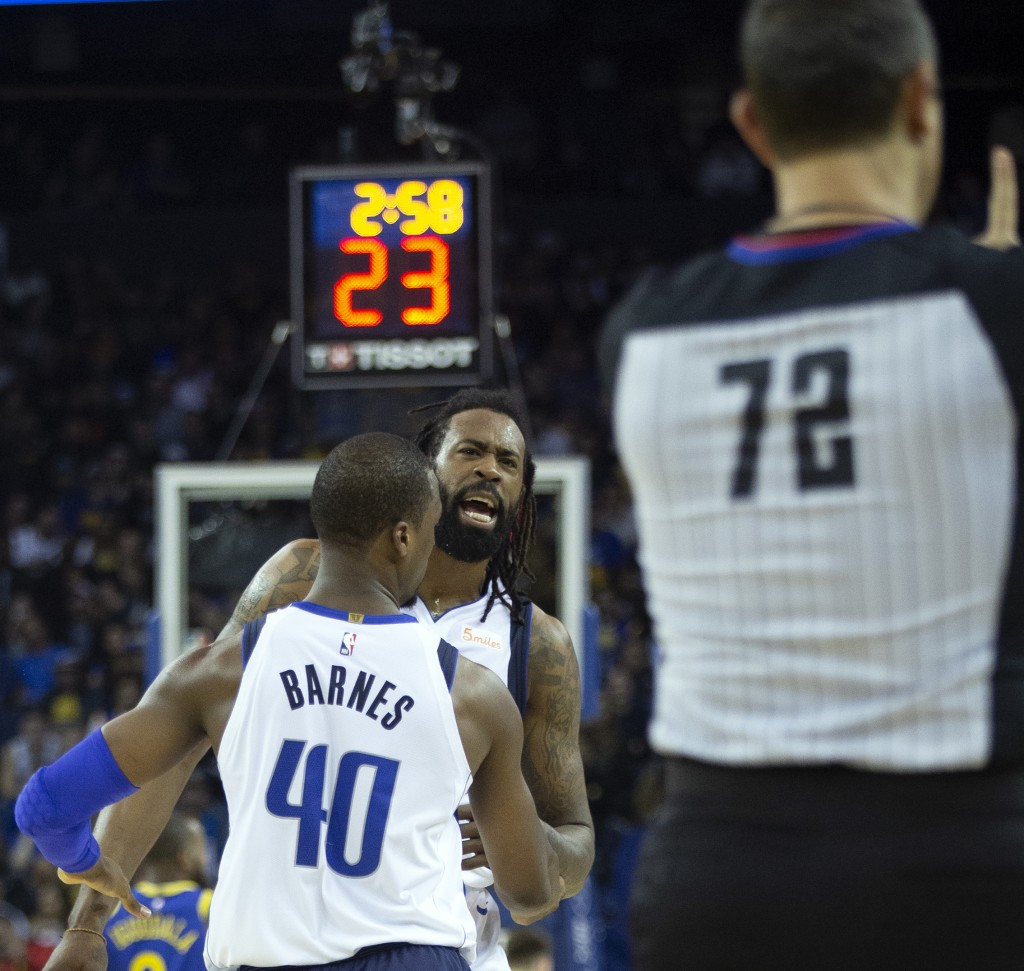 Dallas Mavericks' DeAndre Jordan (6) is held back by teammate Harrison Barnes (40) as he's assessed a technical foul by referee JT Orr (72) during the