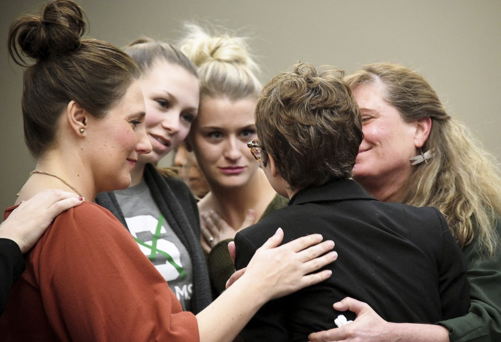 FILE - In this Jan. 19, 2018, file photo, Morgan McCaul gets hugs from other survivors after making her victim impact statement about Larry Nassar in