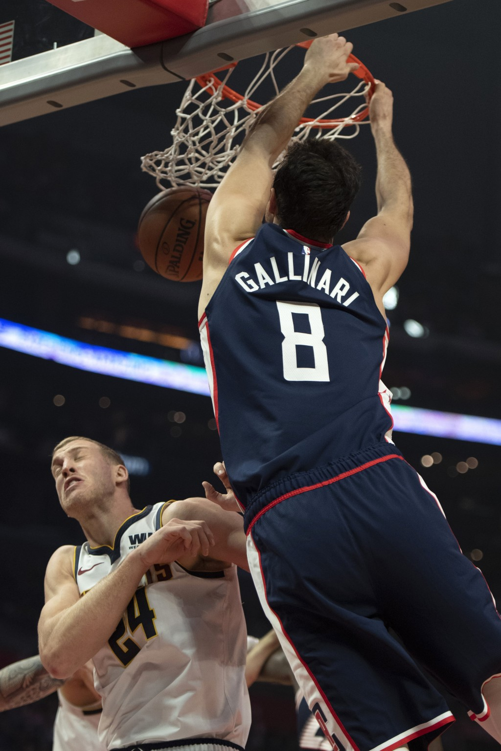 Los Angeles Clippers forward Danilo Gallinari, right, dunks over Denver Nuggets forward Mason Plumlee during the first half of an NBA basketball game