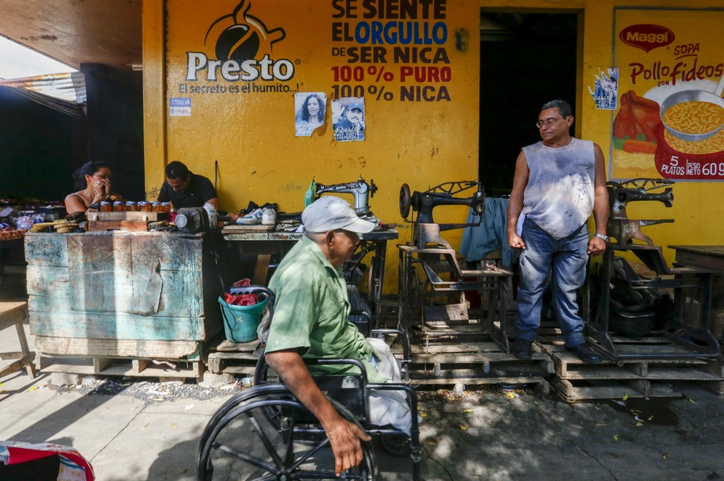 In this Dec. 21. 2018 photo, a man stands outside a tailor shop displaying photos of President Daniel Ortega and his wife and Vice President Rosario M