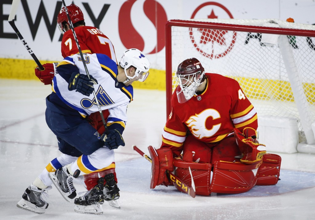 St. Louis Blues' David Perron, center, is hit in the shin by a slap shot as Calgary Flames goalie Mike Smith watches during the third period of an NHL
