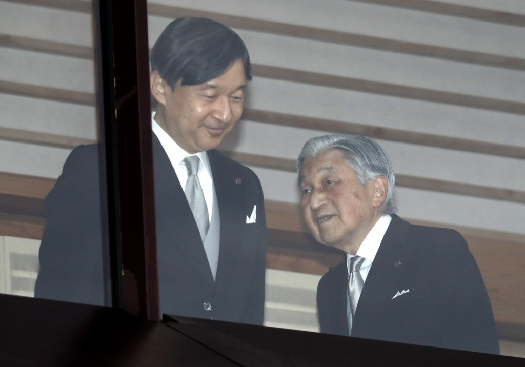 In this Sunday, Dec. 23, 2018, file photo, Japan's Emperor Akihito, right, accompanied by Crown Prince Naruhito, left, walks away after greeting well-...