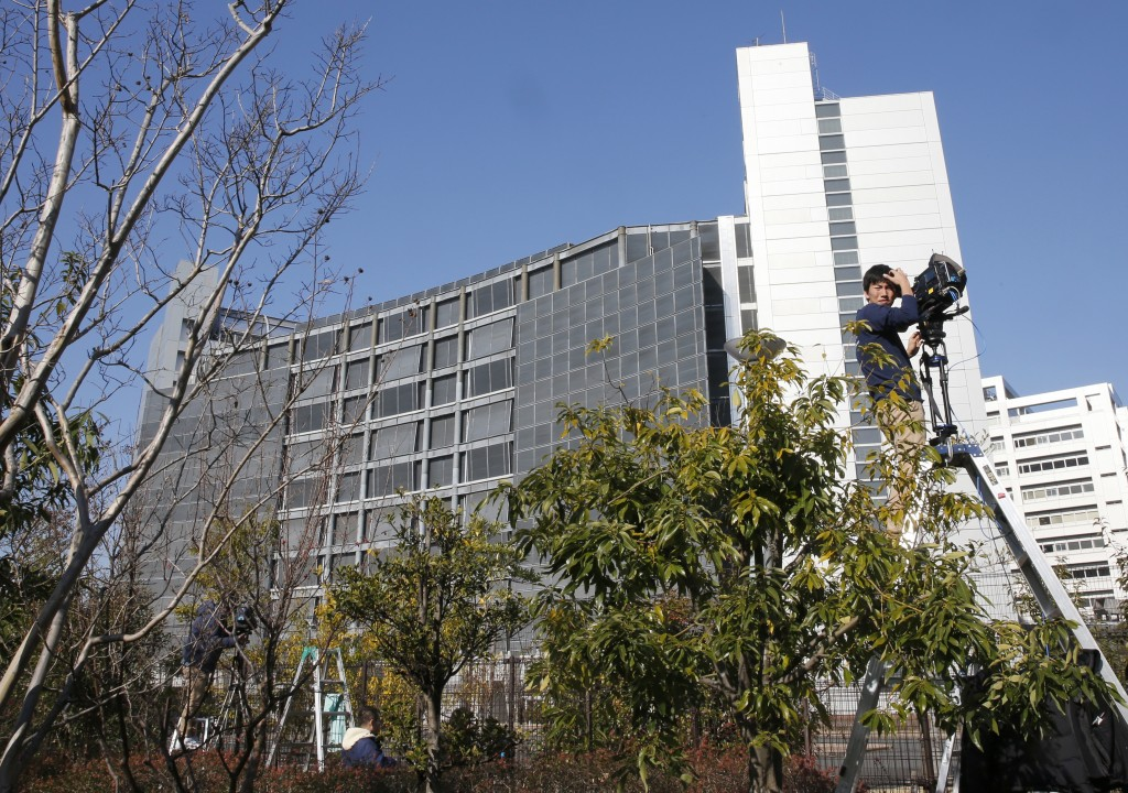 FILE - In this Friday, Dec. 21, 2018, file photo, a cameraman on a ladder stands by outside Tokyo Detention Center, where former Nissan chairman Carlo...