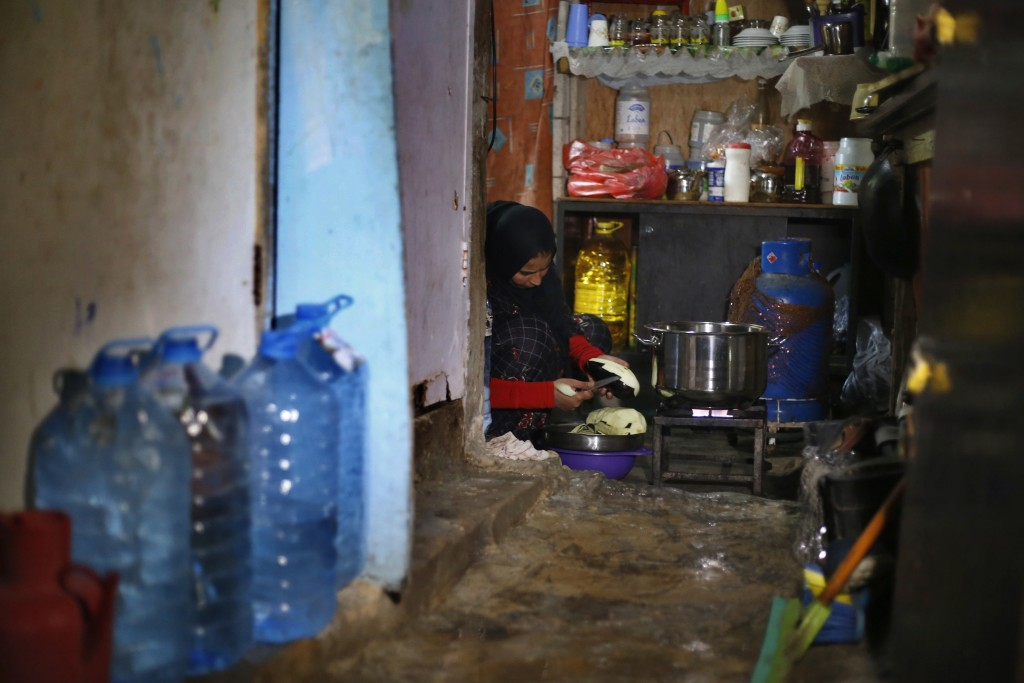 In this Tuesday, Dec. 18, 2018, photo, Syrian refugee Rozan Qarqour prepares lunch at her home in Ouzai refugee compound, in the southern port city of...